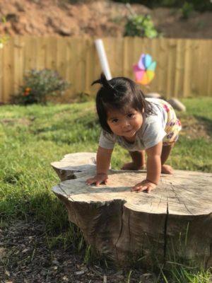 girl climbing on a stump