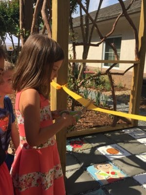 Delaney cuts the ribbon to open the Little Garden that Grew in May, 2018.